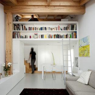 他の地域の小さいコンテンポラリースタイルのおしゃれな独立型ファミリールーム (ライブラリー、白い壁、コンクリートの床、暖炉なし、テレビなし) の写真