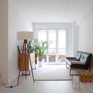 Imagen de sala de estar cerrada, minimalista, de tamaño medio, con paredes blancas, televisor independiente, suelo de madera clara y suelo beige