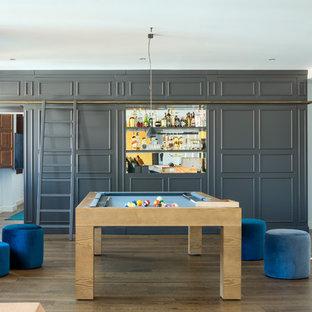 Ejemplo de sala de juegos en casa abierta, ecléctica, con paredes grises, suelo de madera en tonos medios y suelo marrón
