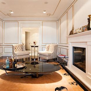 Imagen de sala de estar con barra de bar cerrada, tradicional, de tamaño medio, con paredes blancas, suelo de madera en tonos medios y chimenea tradicional