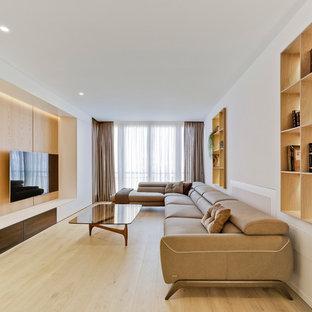 Modelo de sala de estar con biblioteca contemporánea, sin chimenea, con paredes blancas, suelo de madera clara, televisor colgado en la pared y suelo beige