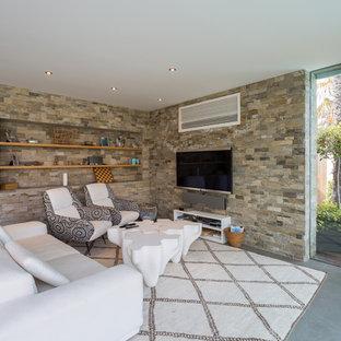 Modelo de sala de estar abierta, actual, de tamaño medio, sin chimenea, con suelo de cemento y televisor colgado en la pared