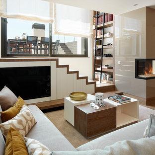 Modelo de sala de estar con biblioteca abierta, contemporánea, de tamaño medio, con paredes beige, chimenea de doble cara, suelo marrón y televisor colgado en la pared