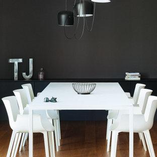 Esempio di una sala da pranzo design di medie dimensioni con pareti nere e pavimento marrone