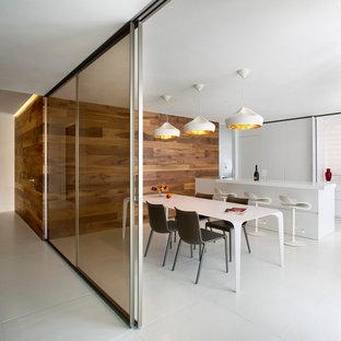 Immagine di una grande sala da pranzo aperta verso la cucina contemporanea con pareti bianche