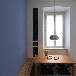Ispirazione per una piccola sala da pranzo aperta verso la cucina minimal con pareti blu, parquet chiaro, camino bifacciale e pavimento beige