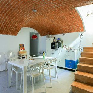 Immagine di una sala da pranzo aperta verso il soggiorno mediterranea di medie dimensioni con pareti bianche