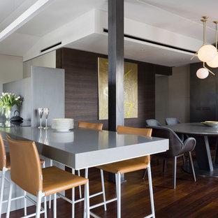 Immagine di una sala da pranzo aperta verso la cucina contemporanea con parquet scuro, pareti multicolore e pavimento marrone
