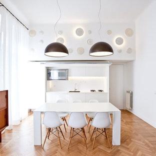 Idee per una sala da pranzo aperta verso la cucina minimalista di medie dimensioni con pavimento in legno massello medio, pavimento marrone e pareti bianche