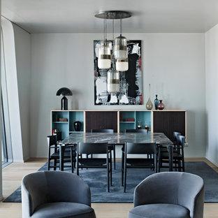 Foto di una sala da pranzo aperta verso il soggiorno minimalista di medie dimensioni con pavimento in legno massello medio, nessun camino, pavimento marrone e pareti bianche