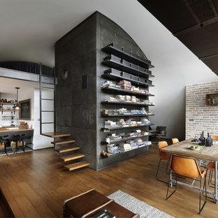 Immagine di una sala da pranzo industriale con pareti bianche e pavimento in legno massello medio