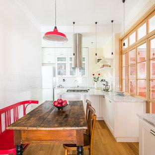 Ejemplo de comedor de cocina tradicional renovado, sin chimenea, con paredes blancas, suelo de madera en tonos medios y suelo azul