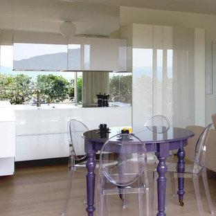 Immagine di una sala da pranzo aperta verso la cucina design con pareti bianche, parquet chiaro e pavimento beige
