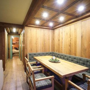 Immagine di una sala da pranzo aperta verso il soggiorno rustica con pareti marroni, pavimento in legno massello medio e pavimento marrone
