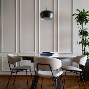 Foto di una sala da pranzo contemporanea con pareti grigie, pavimento in legno massello medio, pavimento marrone e pannellatura