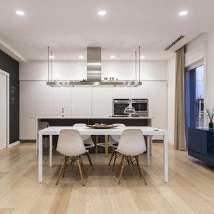 Foto di una sala da pranzo aperta verso la cucina design di medie dimensioni con pareti bianche, parquet chiaro e pavimento beige