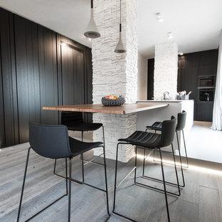Foto di una sala da pranzo design di medie dimensioni con pareti bianche, parquet chiaro e pavimento grigio