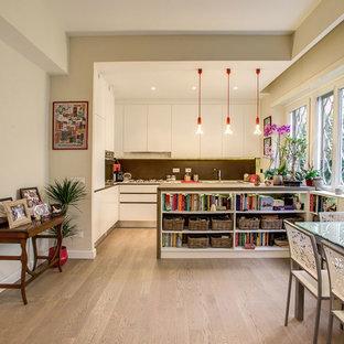 Foto di una sala da pranzo aperta verso la cucina boho chic di medie dimensioni con pareti beige, parquet chiaro e pavimento beige