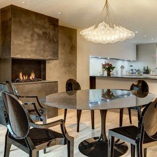 Esempio di una sala da pranzo aperta verso la cucina design con pareti grigie, camino lineare Ribbon e cornice del camino in cemento
