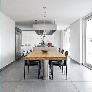 Foto di una sala da pranzo aperta verso la cucina contemporanea con pareti bianche e pavimento grigio