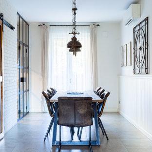 Idee per una sala da pranzo industriale di medie dimensioni con pareti bianche, pavimento in gres porcellanato, pavimento grigio e boiserie