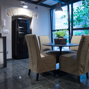 Example of a small urban marble floor and black floor kitchen/dining room combo design in Bari with gray walls