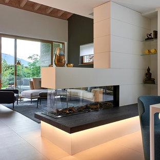 ミラノの広いコンテンポラリースタイルのおしゃれなダイニングキッチン (両方向型暖炉、白い壁、磁器タイルの床、木材の暖炉まわり、グレーの床) の写真