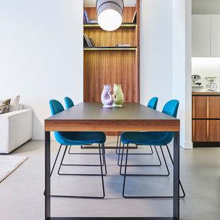 Foto di una sala da pranzo design di medie dimensioni con pareti bianche, pavimento in cemento, nessun camino e pavimento grigio