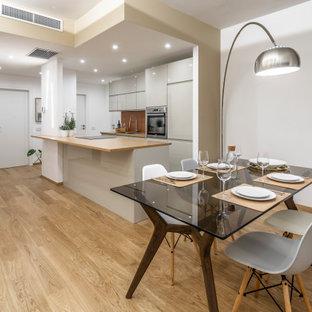 Foto di una sala da pranzo aperta verso la cucina contemporanea di medie dimensioni con pareti bianche, pavimento in legno massello medio e pavimento beige