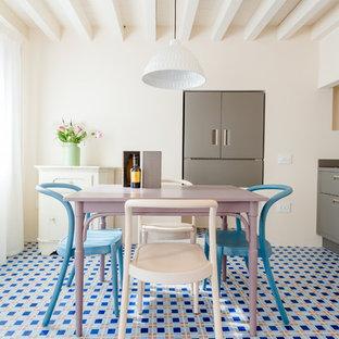 Immagine di una sala da pranzo aperta verso la cucina mediterranea con pareti bianche, pavimento con piastrelle in ceramica e pavimento blu