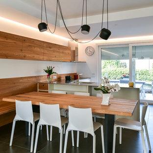 Modelo de comedor de cocina contemporáneo, de tamaño medio, sin chimenea, con paredes blancas, suelo de baldosas de cerámica y suelo negro
