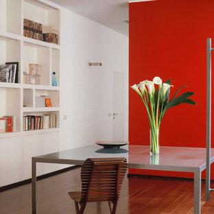 Пример оригинального дизайна: маленькая гостиная-столовая в современном стиле с красными стенами, паркетным полом среднего тона и коричневым полом