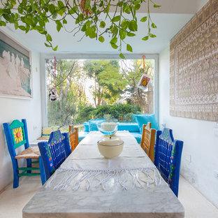 Immagine di una piccola sala da pranzo aperta verso il soggiorno mediterranea con pareti bianche e pavimento beige