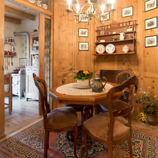 Small country separate dining room in Milan with brown walls, medium hardwood floors and brown floor.