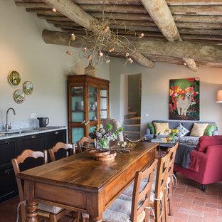 Immagine di una grande sala da pranzo aperta verso il soggiorno country con pareti bianche, pavimento in terracotta e nessun camino
