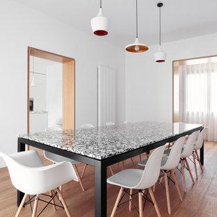 Immagine di una sala da pranzo aperta verso la cucina nordica con pareti bianche e parquet chiaro