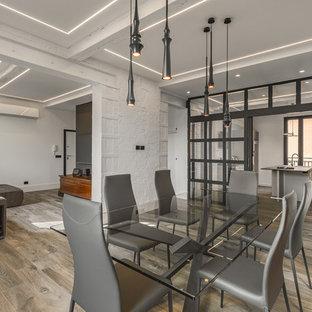 Idee per una sala da pranzo aperta verso il soggiorno industriale con pareti bianche, pavimento in legno massello medio e pavimento marrone