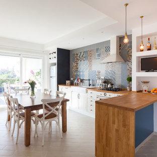Immagine di una sala da pranzo aperta verso la cucina stile marino di medie dimensioni con pareti bianche e pavimento con piastrelle in ceramica