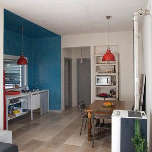 Foto de comedor de cocina minimalista, de tamaño medio, con suelo de piedra caliza, estufa de leña y paredes grises