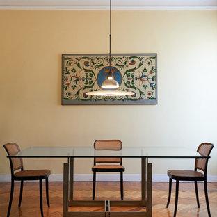 Immagine di una sala da pranzo design chiusa e di medie dimensioni con pareti gialle e pavimento in legno massello medio