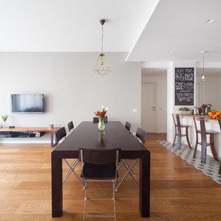 Foto di una grande sala da pranzo aperta verso la cucina minimal con pareti grigie e pavimento in legno massello medio