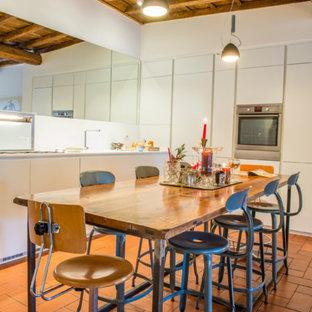 Ejemplo de comedor de cocina bohemio, grande, con suelo rojo, paredes blancas y suelo de ladrillo