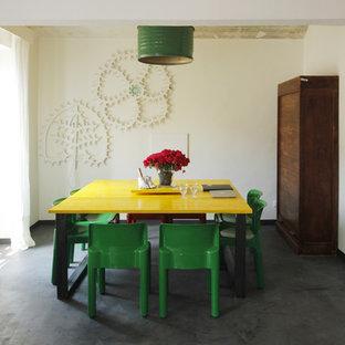 Ispirazione per una sala da pranzo bohémian con pareti bianche, pavimento nero e pavimento in cemento