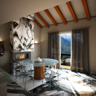 Immagine di un'ampia sala da pranzo aperta verso la cucina minimalista con pareti beige, pavimento in gres porcellanato, camino sospeso, cornice del camino piastrellata e pavimento multicolore