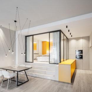 Idee per una sala da pranzo aperta verso il soggiorno design con pareti grigie, parquet chiaro e pavimento beige