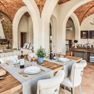 Idéer för att renovera en stor medelhavsstil matplats med öppen planlösning, med beige väggar, klinkergolv i terrakotta, en standard öppen spis och brunt golv