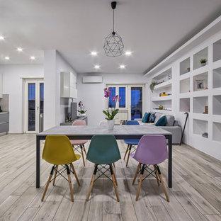 Immagine di una sala da pranzo aperta verso il soggiorno minimal con pareti bianche e pavimento grigio