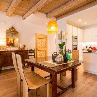 Foto di una sala da pranzo aperta verso la cucina bohémian con pareti bianche, parquet chiaro e pavimento marrone