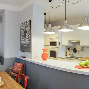 Foto di una sala da pranzo aperta verso la cucina moderna di medie dimensioni con pareti bianche, pavimento in laminato e pavimento grigio
