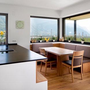 Foto di una sala da pranzo aperta verso la cucina minimal di medie dimensioni con pavimento in legno massello medio, pareti bianche e pavimento beige